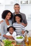 Ethnische Familie, die zusammen Salat zubereitet Stockbild
