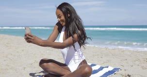 Ethnische Frau auf Tuch unter Verwendung des Telefons stock footage