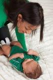 Ethnische Mutter, die mit ihrem Babysohn auf Bett spielt Lizenzfreie Stockfotografie