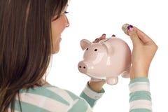 Ethnische weibliche setzende Münze in Piggy Querneigung Stockbilder