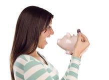 Ethnische weibliche setzende Münze in Piggy Querneigung lizenzfreie stockfotos