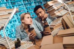 Ethnischer indischer Mischrassekerl und weißes Mädchen umgeben durch Bücher in der Bibliothek Studenten trinken Kaffee lizenzfreies stockfoto