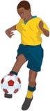 Ethnischer Junge, der einen Fußball tritt Stockbild