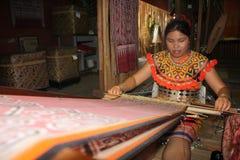 Ethnischer Mann, der Armbänder iban herstellt stockfotos