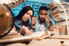 Ethnisches asiatisches Mädchen und indischer Mischrassekerl umgeben durch Bücher in der Bibliothek Studenten sind Lesebuch lizenzfreies stockfoto