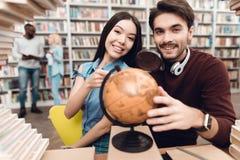 Ethnisches asiatisches Mädchen und weißer Kerl umgeben durch Bücher in der Bibliothek Studenten benutzen Kugel stockfotografie