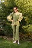 Ethno clothes, outdoors, green color, one young adult woman posi Royalty Free Stock Image
