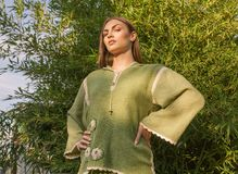 Ethno clothes, outdoors, green color, one young adult woman posi Royalty Free Stock Photography