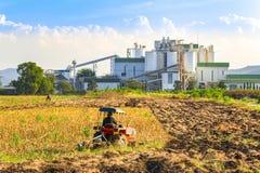 Ethylalcohol industriële raffinaderij met landbouwbedrijftractoren in de voorgrond Royalty-vrije Stock Foto