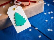 Etichetta bianca con l'immagine dell'abete di Natale su un regalo con un nastro rosso Immagini Stock Libere da Diritti