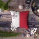 Etichetta del buon anno con la bandiera di Malta sul cuscino Concetto della decorazione di Natale sulla tavola di legno con gli o immagine stock libera da diritti