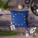 Etichetta del buon anno con la bandiera di Unione Europea sul cuscino Concetto della decorazione di Natale sulla tavola di legno  fotografie stock libere da diritti