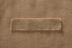 Etichetta del pezzo della struttura del tessuto della tela da imballaggio sopra la tela di iuta della tela del panno di sacco fotografia stock