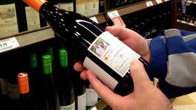 Etichetta della lettura dell'uomo di vino rosso dallo scaffale stock footage