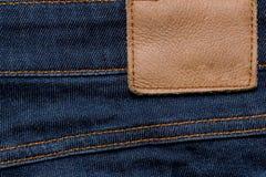 Etichetta di cuoio in bianco dei jeans sull'blue jeans Immagine Stock