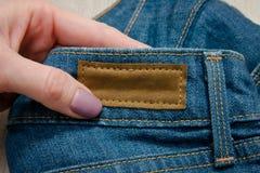 Etichetta di cuoio sui jeans in mano femminile Fotografia Stock Libera da Diritti