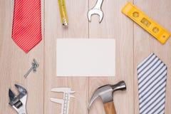 Etichetta di giorno di padri con gli strumenti ed il frame dei legami su legno Immagine Stock