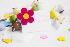 Etichetta felice di Pasqua con le uova di Pasqua, i fiori, i coniglietti e le piume Fotografia Stock