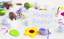 Etichetta felice di Pasqua con le uova di Pasqua, i fiori, i coniglietti e le piume Immagini Stock