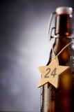 Etichetta a forma di stella con il numero del 24 dicembre intorno alla bottiglia Fotografie Stock