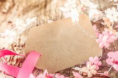 Etichetta marrone in bianco del regalo con il fiore delicato della molla Fotografie Stock Libere da Diritti