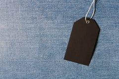 Etichetta nera vuota sul fondo del denim Spazio vuoto del testo fotografia stock libera da diritti