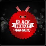 Etichetta rossa di Black Friday con i nastri sul fondo del bokeh Fotografia Stock