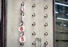 Etichette di numeri che appendono in un vecchio gabinetto Fotografia Stock Libera da Diritti