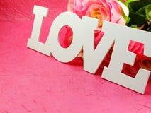 Etichetti con le parole con amore ed è aumentato su fondo rosa Fotografia Stock Libera da Diritti