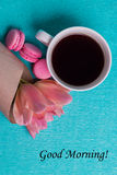 Etichetti il buongiorno, i tulipani rosa, la tazza di caffè ed i maccheroni rosa Fotografie Stock