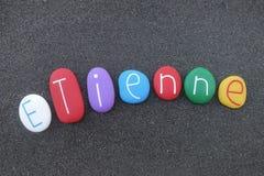 Etienne, nome dado feminino francês com as pedras coloridas sobre a areia vulcânica preta foto de stock royalty free