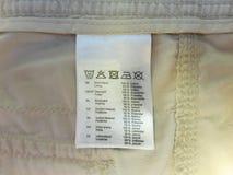 Etikett av kläder med tydliga material och tvättande symboler arkivbilder