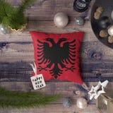 Etikett f?r lyckligt nytt ?r med den Albanien flaggan p? kudden Julgarneringbegrepp p? tr?tabellen med ?lskv?rda objekt royaltyfri foto