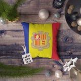 Etikett f?r lyckligt nytt ?r med den Andorra flaggan p? kudden Julgarneringbegrepp p? tr?tabellen med ?lskv?rda objekt arkivfoto