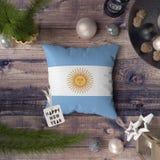 Etikett f?r lyckligt nytt ?r med den Argentina flaggan p? kudden Julgarneringbegrepp p? tr?tabellen med ?lskv?rda objekt arkivfoton