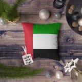 Etikett f?r lyckligt nytt ?r med den F?renade Arabemiraten flaggan p? kudden Julgarneringbegrepp p? tr?tabellen med ?lskv?rda obj arkivfoto