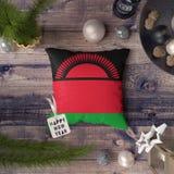 Etikett f?r lyckligt nytt ?r med den Malawi flaggan p? kudden Julgarneringbegrepp p? tr?tabellen med ?lskv?rda objekt fotografering för bildbyråer