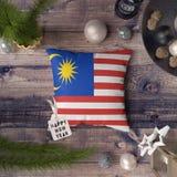 Etikett f?r lyckligt nytt ?r med den Malaysia flaggan p? kudden Julgarneringbegrepp p? tr?tabellen med ?lskv?rda objekt arkivbild