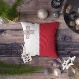 Etikett f?r lyckligt nytt ?r med den Malta flaggan p? kudden Julgarneringbegrepp p? tr?tabellen med ?lskv?rda objekt royaltyfri bild