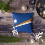 Etikett f?r lyckligt nytt ?r med den Marshall Islands flaggan p? kudden Julgarneringbegrepp p? tr?tabellen med ?lskv?rda objekt arkivbild