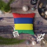 Etikett f?r lyckligt nytt ?r med den Mauritius flaggan p? kudden Julgarneringbegrepp p? tr?tabellen med ?lskv?rda objekt royaltyfri foto