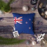 Etikett f?r lyckligt nytt ?r med den Nya Zeeland flaggan p? kudden Julgarneringbegrepp p? tr?tabellen med ?lskv?rda objekt arkivbilder