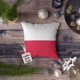Etikett f?r lyckligt nytt ?r med den Polen flaggan p? kudden Julgarneringbegrepp p? tr?tabellen med ?lskv?rda objekt royaltyfri bild
