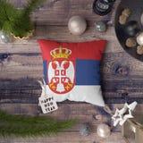 Etikett f?r lyckligt nytt ?r med den Serbien flaggan p? kudden Julgarneringbegrepp p? tr?tabellen med ?lskv?rda objekt royaltyfri fotografi