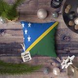 Etikett f?r lyckligt nytt ?r med den Solomon Islands flaggan p? kudden Julgarneringbegrepp p? tr?tabellen med ?lskv?rda objekt arkivbild