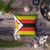 Etikett f?r lyckligt nytt ?r med den Zimbabwe flaggan p? kudden Julgarneringbegrepp p? tr?tabellen med ?lskv?rda objekt arkivbild