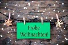 Etikett med Frohe Weihnachten, snöig bakgrund Arkivfoto