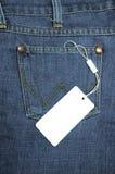 Etikett som binds till jeansen Arkivfoto