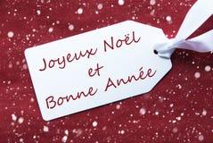 Etiketten på röd bakgrund, snöflingor, Bonne Annee betyder nytt år Royaltyfria Foton