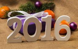 Etikettieren Sie 2016, Geschenk mit Postkarte und Weihnachtsdekorationen Lizenzfreies Stockfoto